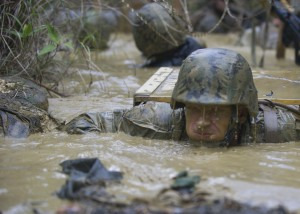 160112-N-YG415-115 OKINAWA, Japan (Jan. 12, 2016) Ensign Frank S. Sysko assigned to Naval Mobile Construction Battalion (NMCB) 3 holds his breath while he exits a mud-filled trench during a jungle warfare training evolution hosted by Marines with the Jungle Warfare Training Center (JWTC). The JWTC endurance course tests the Seabees will, stamina and the ability to work together as a team. NMCB 3 is deployed to several countries in the Pacific area of Operations conducting construction operations and humanitarian assistance projects. (U.S. Navy photo by Mass Communication Specialist 1st Class Michael Gomez/Released)