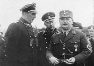 Der große SS-Schutz-Staffel-Appell der Gruppe Ost der SS. in Berlin! Der Stabschef Hauptmann [Ernst] Röhm, (rechts) der Reichsführer der SS. [Heinrich] Himmler, (mitte) und der Gruppenführer der Gruppe Ost der SS. [Kurt] Daluege, (links) beim Gespräch im Lager in Döberitz. August 1933 (Ausschnitt)